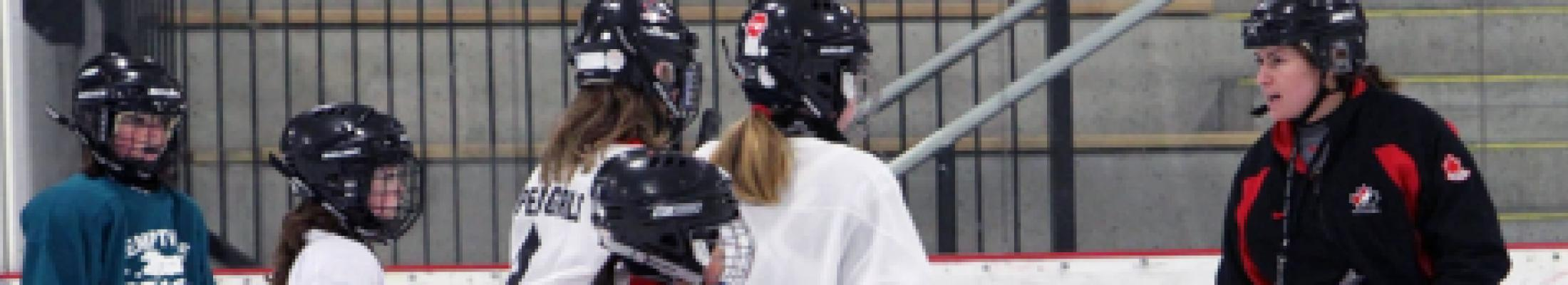 woman coaching girls hockey team